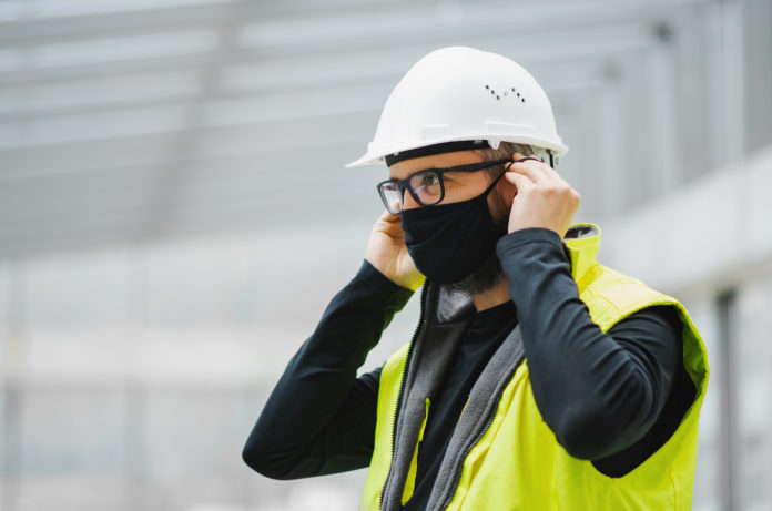 Side view portrait of worker with face mask at the airport.